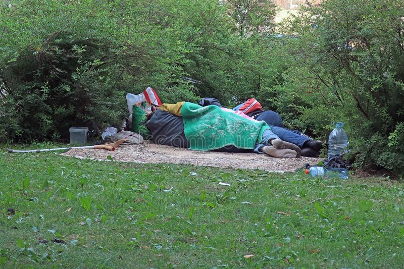 Homeless people sleeping on the lawn royalty free stock images