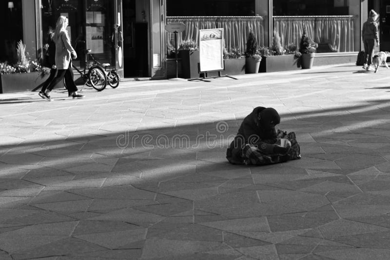 Homeless people on the street of a European city begging for money. Black and white image. Street photography. Homeless people on the street of a European city royalty free stock photography