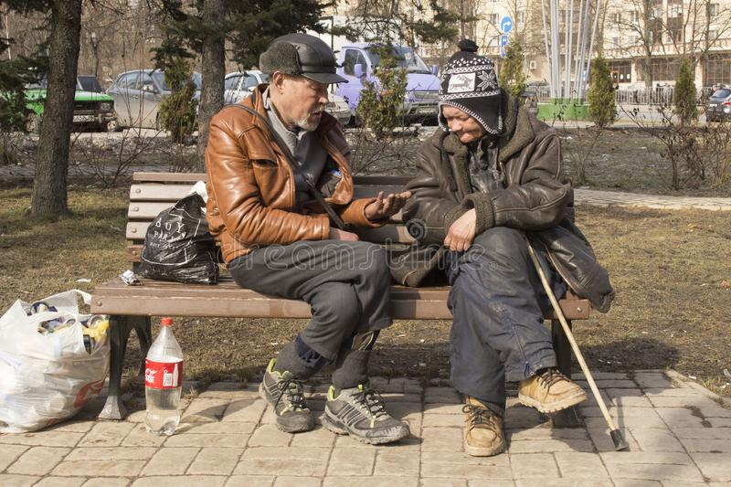 Homeless people on the street. Poverty in the Third World. Woman and man live on the street. Disadvantage and poverty. Vices of capitalism. Food and water for royalty free stock image