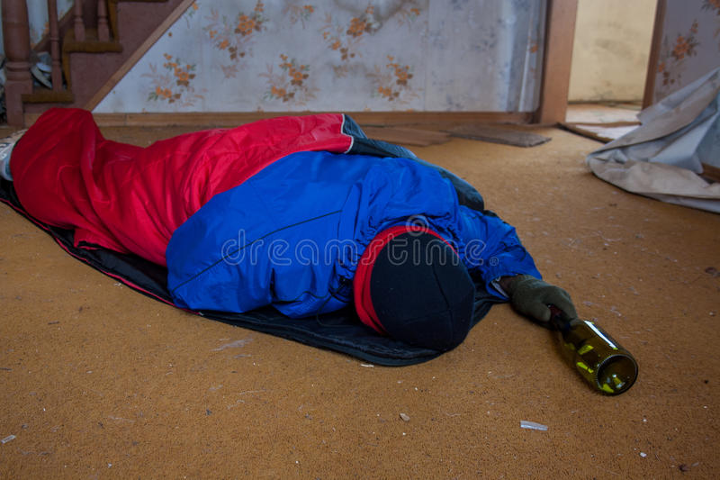 Homeless person. Homeless man wrap up in a sleeping bag royalty free stock photo
