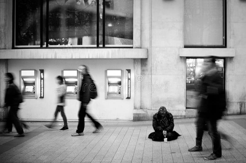 A Homeless Person Begging on the Champs Elysees. A powerful black and white image of a homeless person begging for money on the busy Champs Elysees avenue in stock photos