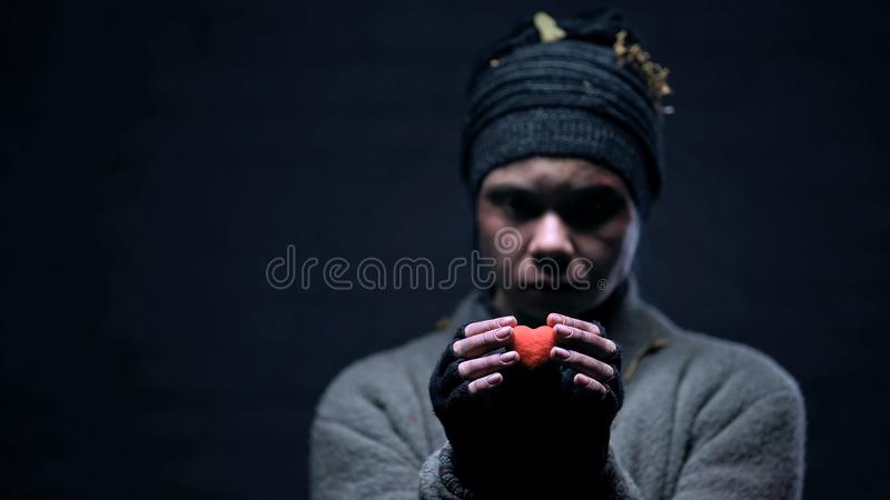 Homeless person holding red toy heart in hands, hope for better life, charity royalty free stock photo