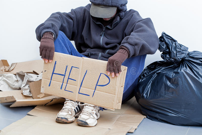 Homeless person sitting on the ground stock photos