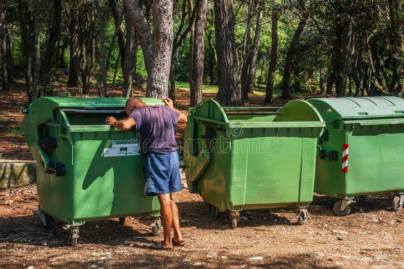 Homeless digging in green dumpsters in the city, summer Sunny day royalty free stock images