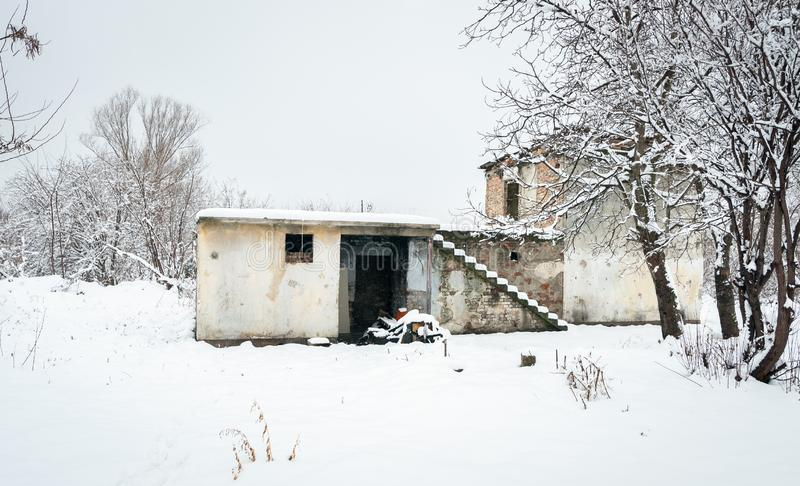 Old abandoned ruin house without windows and roof used as homeless shelter during the summer empty on the cold winter days with sn stock photo