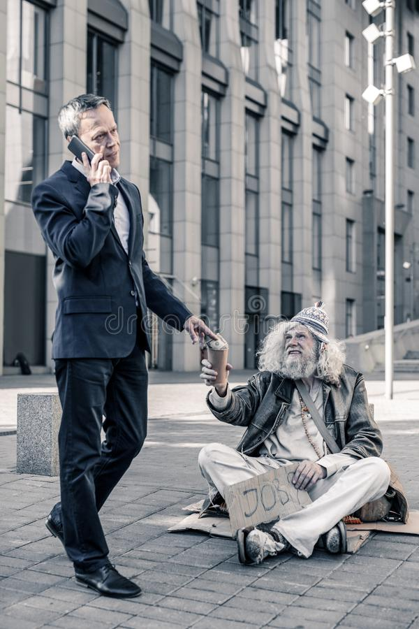 Indifferent rich man talking on smartphone and sharing money with homeless. Homeless sitting. Indifferent rich men talking on smartphone and sharing money with stock photo