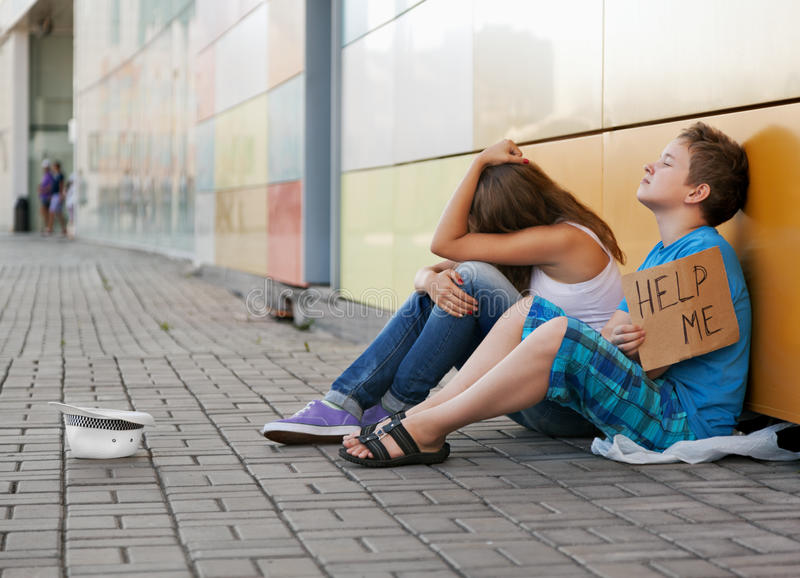 Homelessness. Homeless teenage boy and girl begging in street (The production scene; problem-free children play a role of beggars royalty free stock image