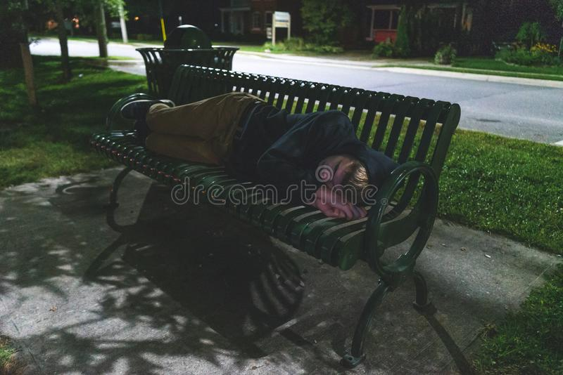 Homeless teenager sleeping on a park bench. stock images