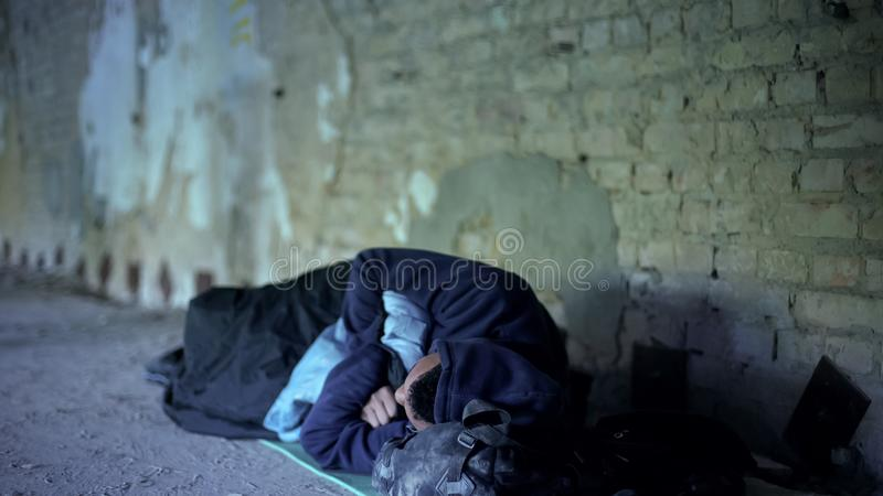 Homeless teenager sleeping on street, poverty, indifferent egoistic society stock photography