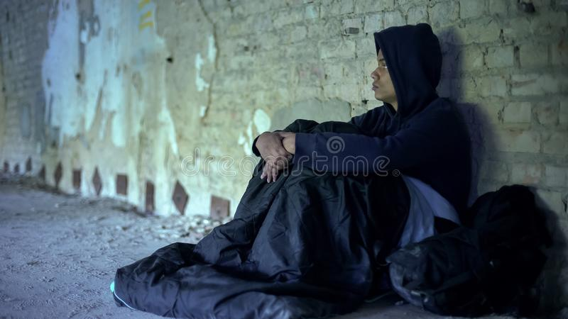 Homeless teenager watching people passing by indifferently, abandoned by society. Stock photo stock photography