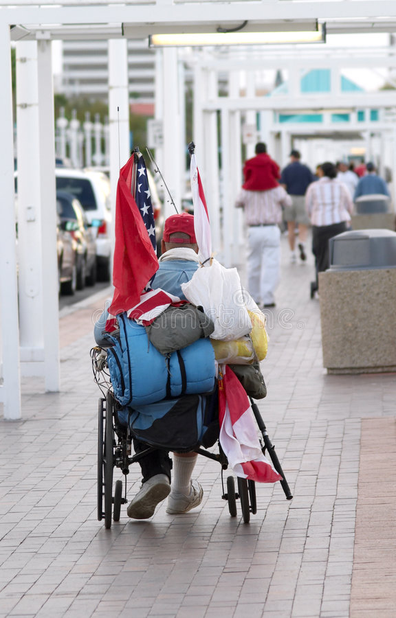 Homeless Vet. A homeless veteran in a wheelchair with a flag royalty free stock images