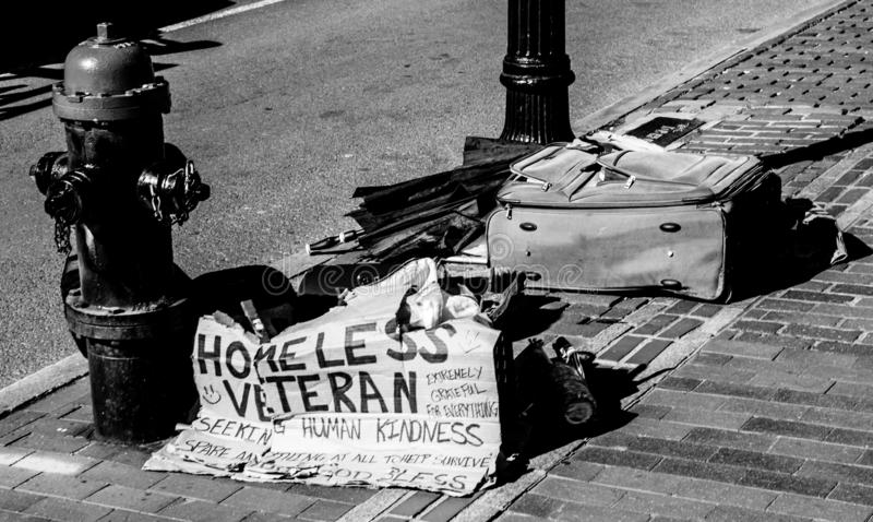 Homeless Veteran sign and belongings on Boston city street. A sign seeking help and the belongings of a homeless veteran are seen on the public city streets of royalty free stock photo