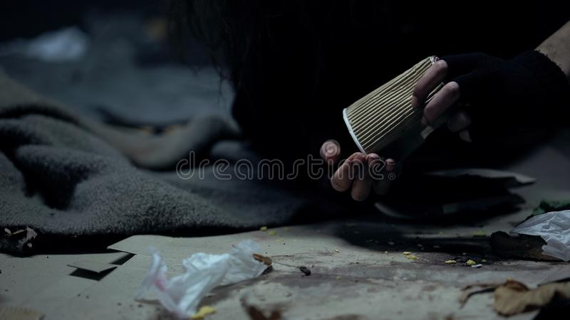 Homeless woman throwing coins from paper cup, counting donations, charity stock photo