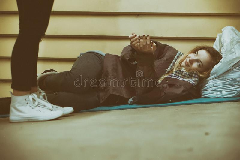 Homeless young teen receiving help by a stranger stock images