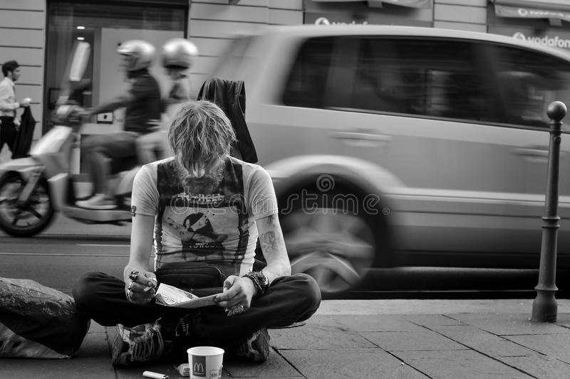 Homelessness challenges the modern world. Foreground of ahomeless reading a book while smoking a cigarette. while in the background there is a scene of daily stock image