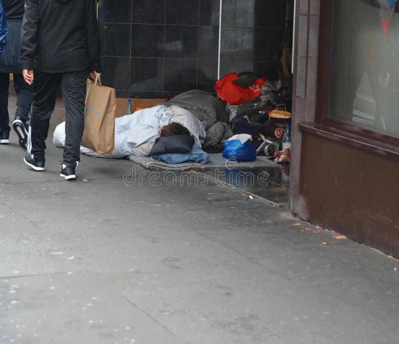 Homelessness. Two homeless people sleeping in a doorway in the city during the day, Manchester UK stock image