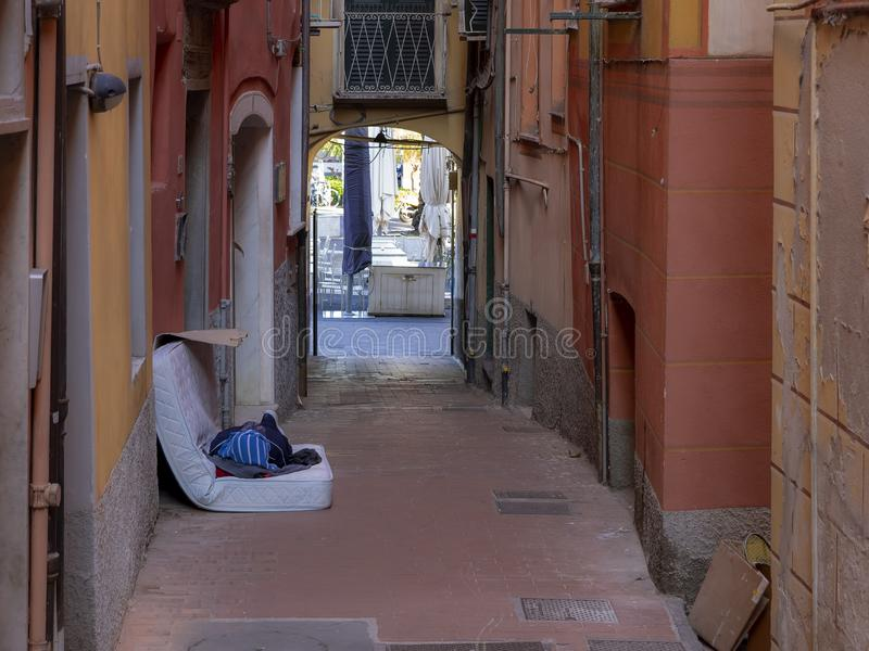 Homelessness. Unidentifiable man sleeps on old mattress in the street, Italy - Lerici. Homelessness. Unidentifiable man sleeps on an old mattress in the street royalty free stock photos
