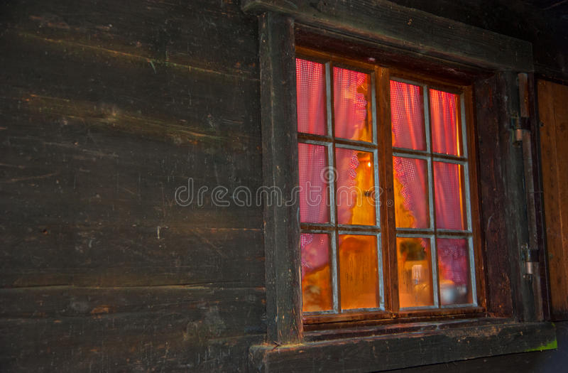 Homely vibe behind the window with glazing bars of a log cabin. Atmospherically exterior shot of a log cabin with a window with glazing bars in the evening royalty free stock images