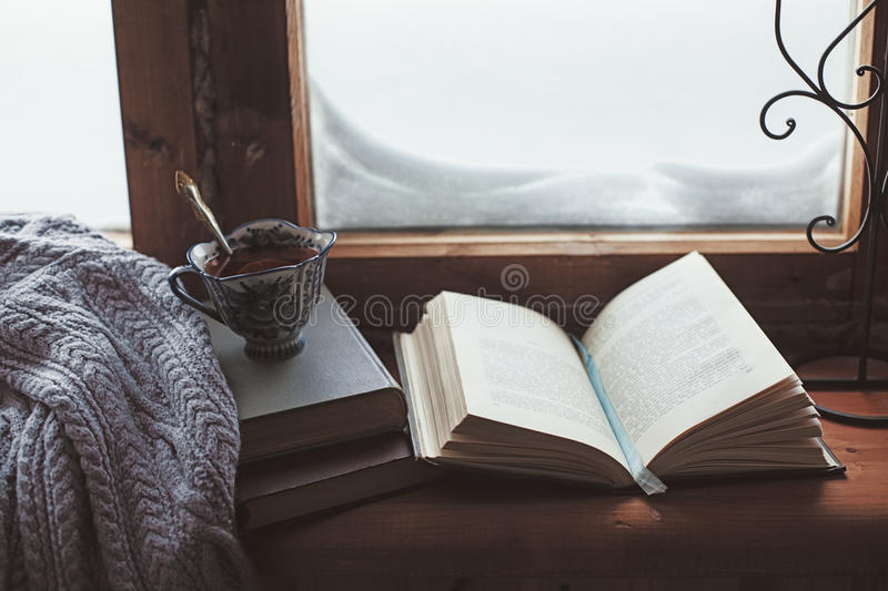 Homely wnter concept of window sill. Warm and comfy winter concept. Book, cup of lemon tea and sweater on wooden window sill in old house. Reading and relaxing stock image