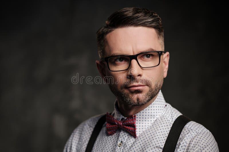 Homem à moda com os suspensórios vestindo do laço e levantamento no fundo escuro fotografia de stock