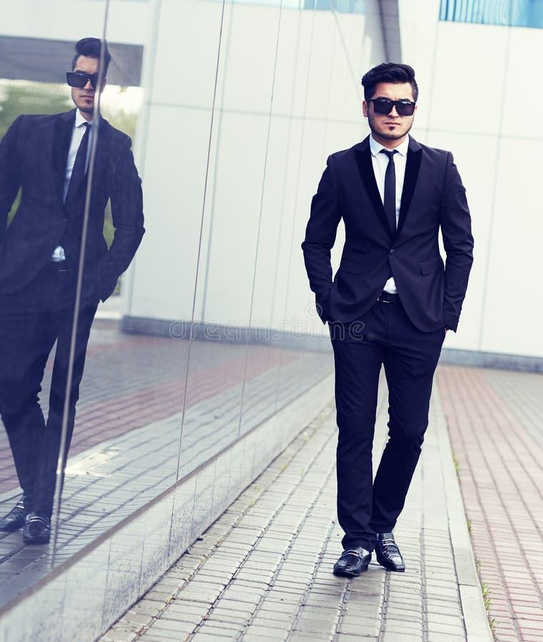 Homem à moda considerável no terno e em óculos de sol pretos elegantes fotografia de stock