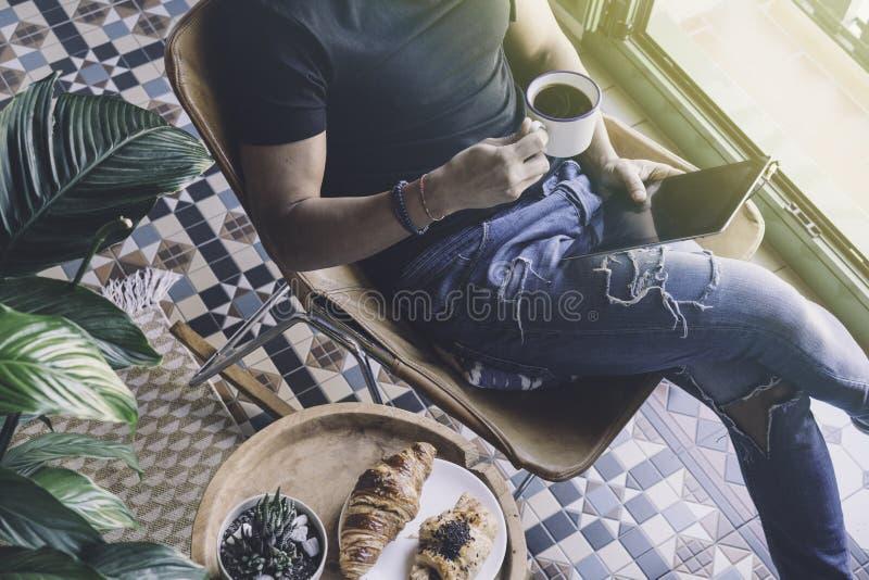 Homem à moda considerável nos fones de ouvido que escuta a música na tabuleta eletrônica e na xícara de café bebendo em casa ocas foto de stock