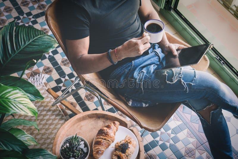Homem à moda considerável nos fones de ouvido que escuta a música na tabuleta eletrônica e na xícara de café bebendo em casa ocas fotografia de stock