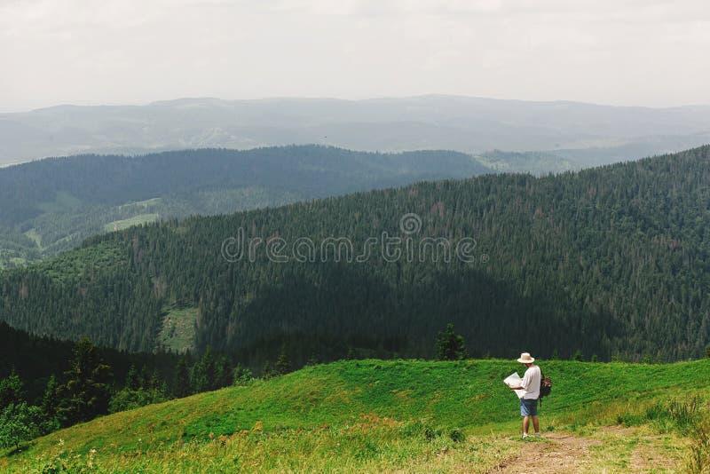 Homem à moda do viajante do moderno que guarda o mapa e que anda na surpresa imagens de stock