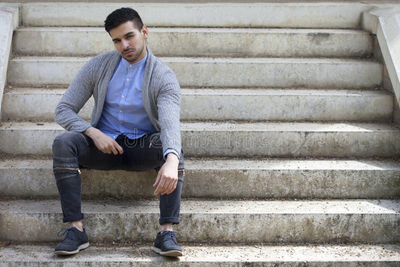 Homem à moda na camiseta com a barba que senta-se em escadas imagens de stock royalty free