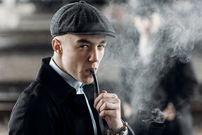 Homem à moda no equipamento retro, tubulação de madeira de fumo holme do sherlock imagem de stock royalty free