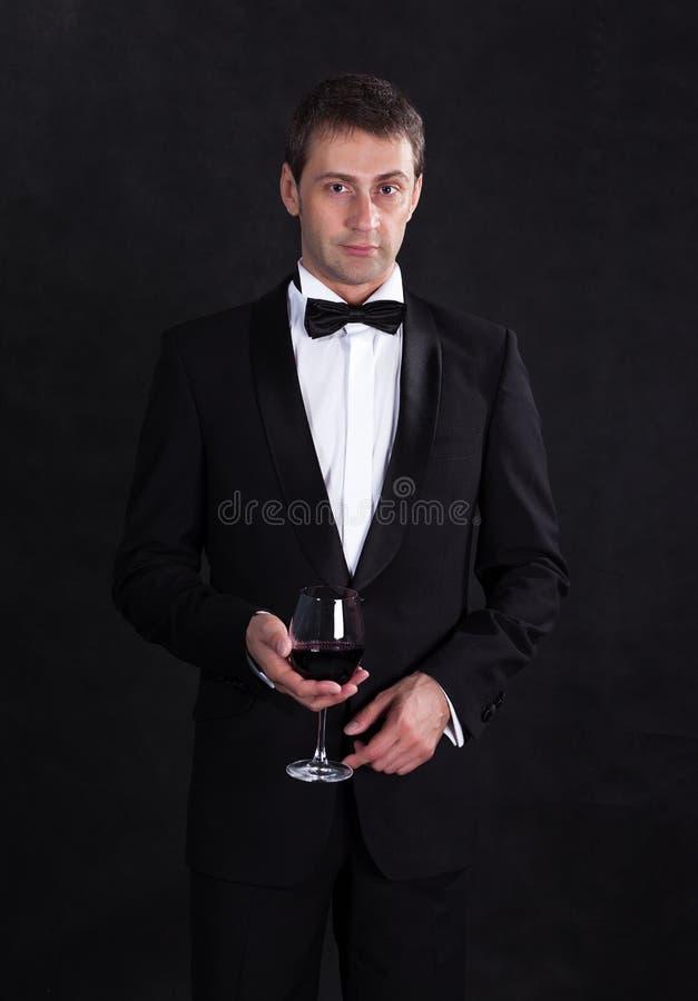 Homem à moda no smoking preto elegante com vinho tinto de vidro foto de stock royalty free