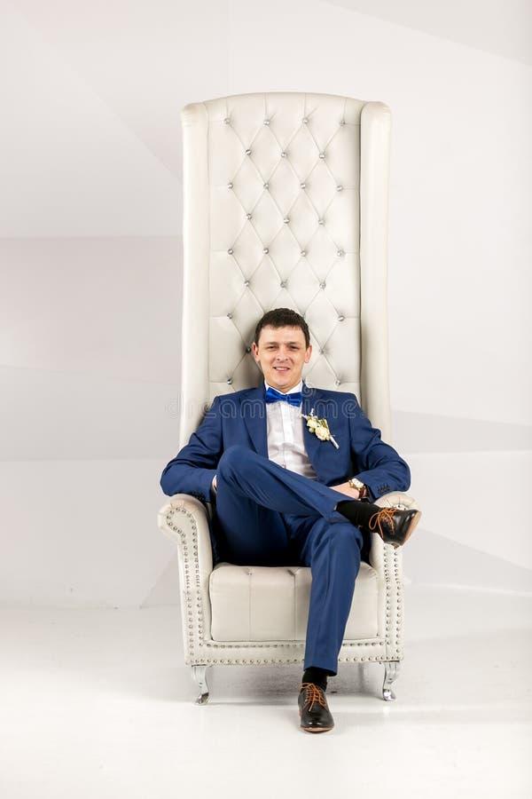 Homem à moda no terno azul que levanta na poltrona branca no estúdio fotos de stock royalty free
