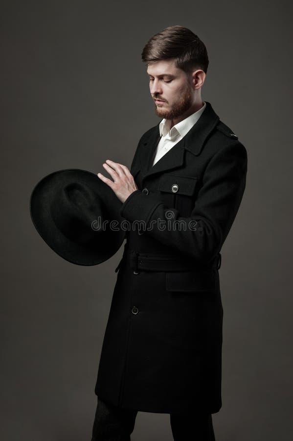 Homem à moda novo com barba e pensamento olhando o chapéu imagens de stock royalty free