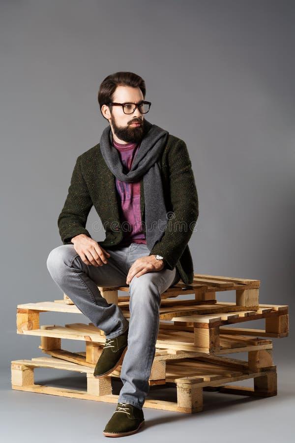 Homem à moda novo com a barba, vestindo um revestimento que senta-se em páletes imagens de stock royalty free