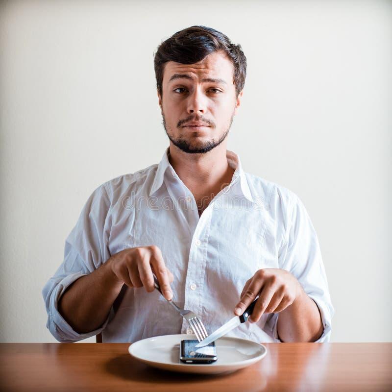 Homem à moda novo com camisa e o telefone brancos no prato fotografia de stock