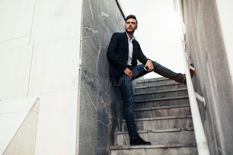 Homem à moda novo do homem de negócios com uma barba em um terno elegante e em calças de brim imagem de stock