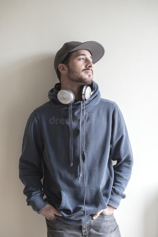 Homem à moda novo que escuta a música imagens de stock