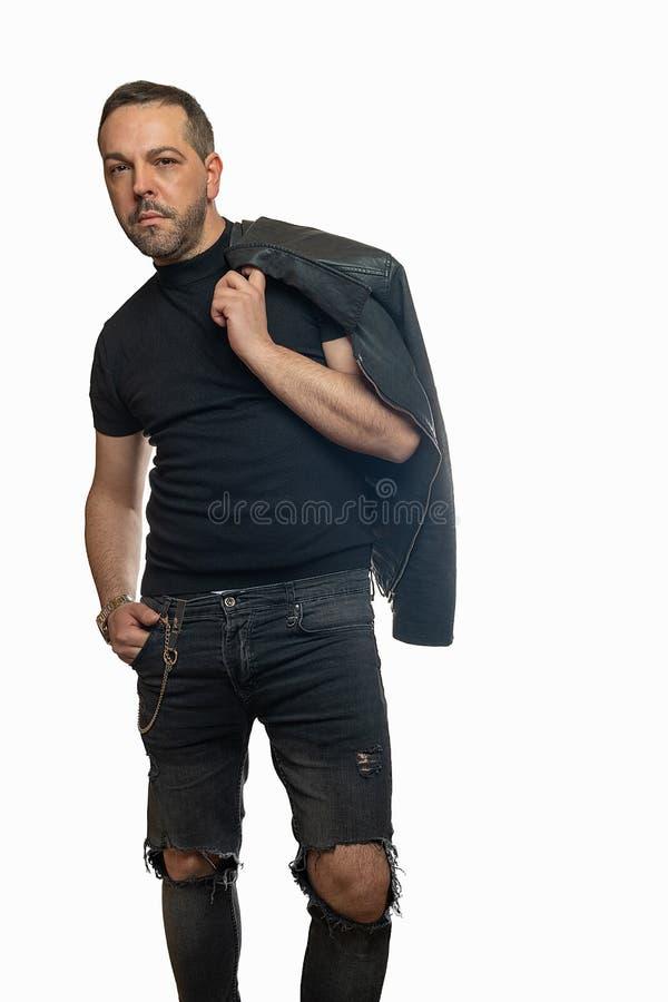 Homem à moda que levanta com o casaco de cabedal jogado sobre imagens de stock