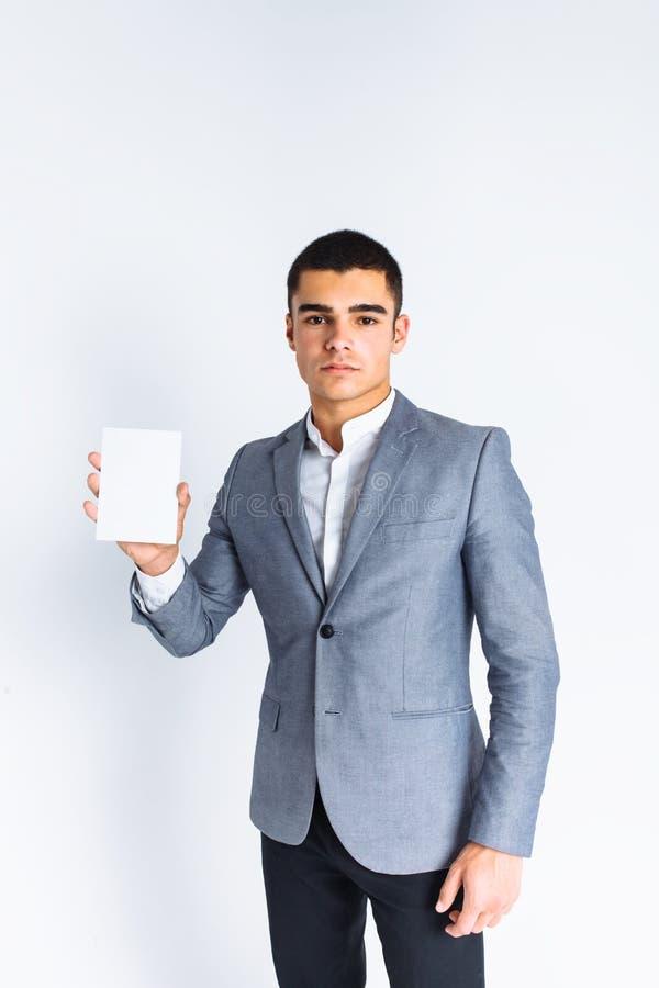 Homem à moda que mostra o cartão branco vazio, isolado, homem no fundo branco no estúdio fotografia de stock royalty free