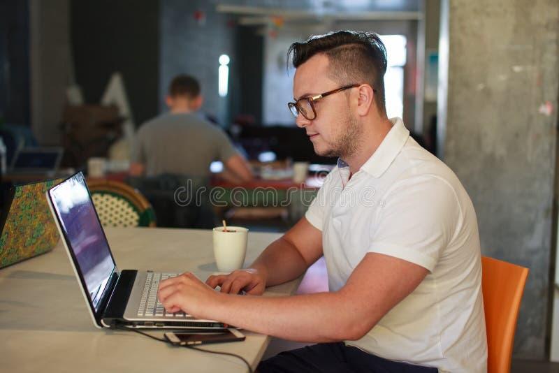 Homem à moda que usa o portátil no escritório imagens de stock