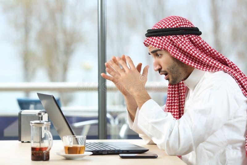 Homem árabe chocado que verifica o portátil em uma barra fotos de stock royalty free
