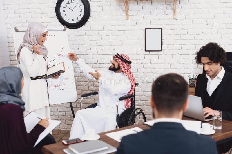 Homem árabe deficiente na cadeira de rodas que trabalha no escritório O homem e o colega de trabalho fêmea estão fazendo o presen foto de stock royalty free