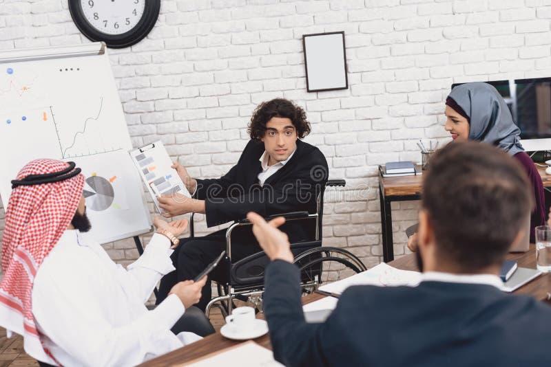 Homem árabe deficiente na cadeira de rodas que trabalha no escritório O homem está apresentando cartas no whiteboard foto de stock royalty free