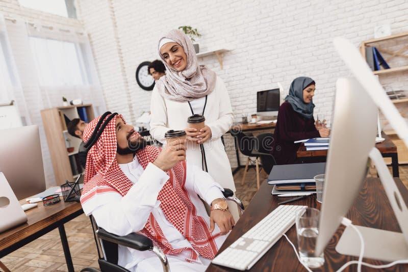 Homem árabe deficiente na cadeira de rodas que trabalha no escritório O homem está bebendo o coffe com colega de trabalho fêmea foto de stock