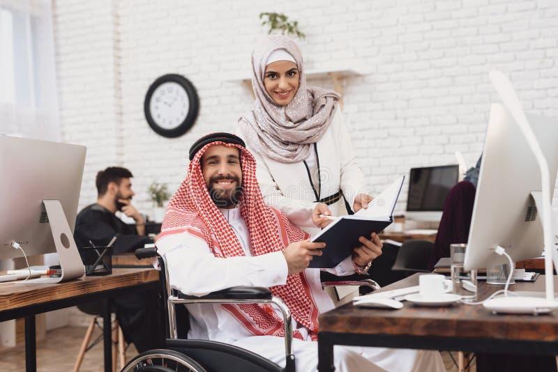 Homem árabe deficiente na cadeira de rodas que trabalha no escritório O homem está compartilhando de notas com o colega de trabal fotos de stock royalty free