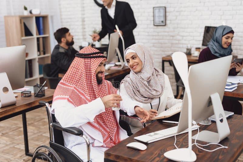 Homem árabe deficiente na cadeira de rodas que trabalha no escritório O homem está discutindo o trabalho com o colega de trabalho imagens de stock