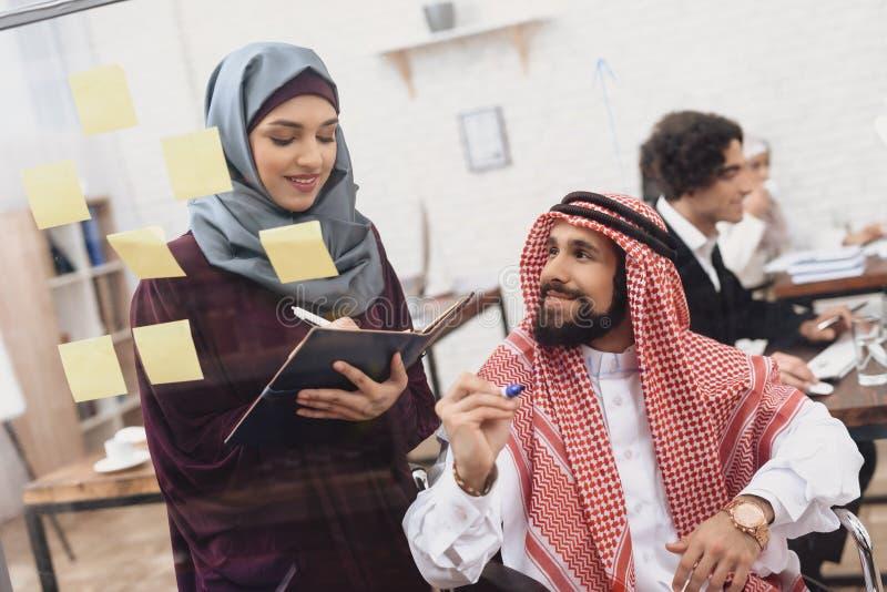 Homem árabe deficiente na cadeira de rodas que trabalha no escritório O homem está escrevendo notas na placa de vidro imagem de stock royalty free