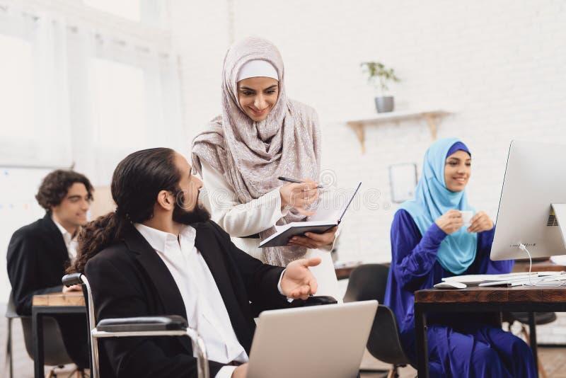 Homem árabe deficiente na cadeira de rodas que trabalha no escritório O homem está falando ao colega de trabalho fêmea foto de stock royalty free
