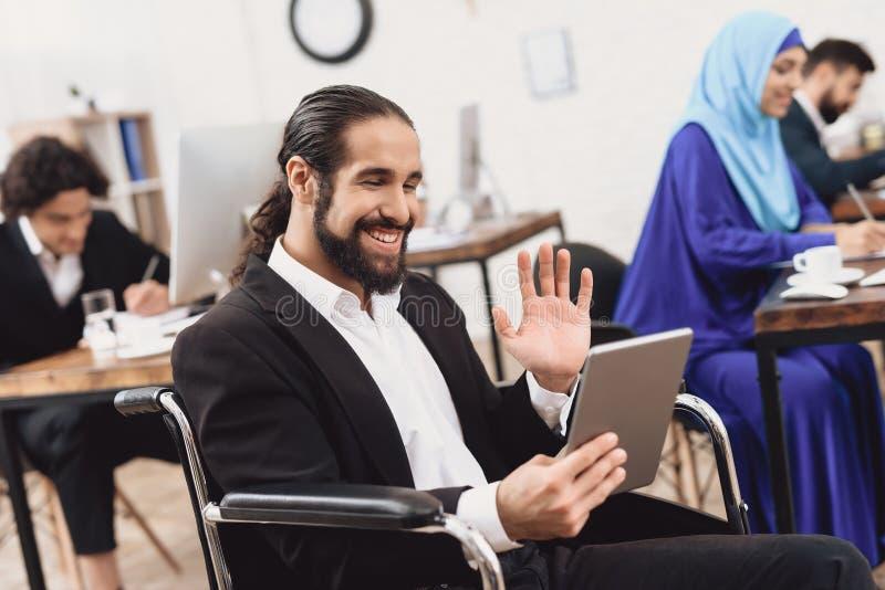 Homem árabe deficiente na cadeira de rodas que trabalha no escritório O homem está falando na tabuleta imagens de stock