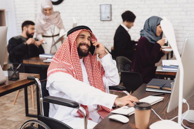 Homem árabe deficiente na cadeira de rodas que trabalha no escritório O homem está falando no telefone imagens de stock